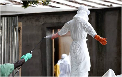 An Ebola medical personnel being sprayed with disinfectant