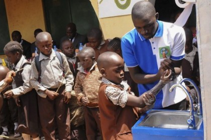 Pupil Washing hands under guidance of a Teacher at a Primary School in Lagos