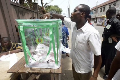 Lagos, NIGERIA: A man drops his voters card in a ballot box at a polling station in Lagos 14 April 2007. Nigerians voted 14 April in elections for  governors and legislators in 36 states, with security forces on high alert and violence reported in two southern oil towns. Major parties see the polls as an indicator of their chances in the April 21 election of a successor to President Olusegun Obasanjo, who is ending his second four-year term.      AFP PHOTO / PIUS UTOMI EKPEI (Photo credit should read PIUS UTOMI EKPEI/AFP/Getty Images)