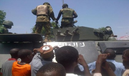 Troops stand on September 16, 2014 in Maiduguri on a armored personnel carrier recovered from Boko Haram