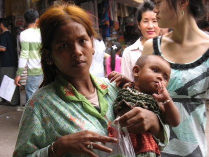 A woman in Cambodia carrying a child for treatment(PHOTO: Internet)
