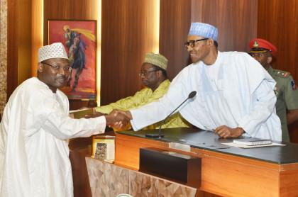 President Muhammadu Buari shaking hands with the sworn-in INEC Chairman Prof. Mahmood Yakubu,