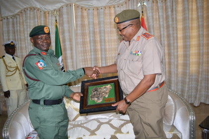 Generals Shoke and Olonisakin exchanging souvenir