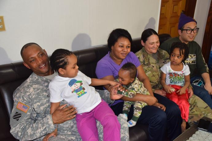 The Enyioko family visit with 1st Sgt. Melanie Scott and Master Sgt. Michael Henry, senior noncommissioned officers assigned to Headquarters. PHOTO: Kcrg.com