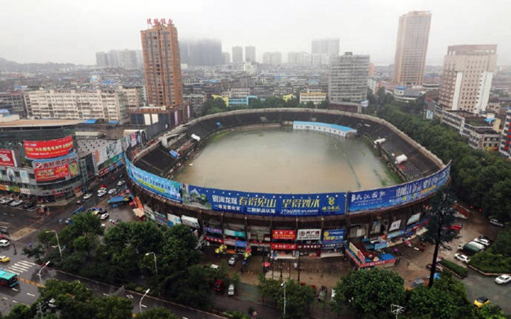 Pic shows:  The flooded stadium. Continuous rainfall in a Chinese city has caused flooding in a football stadium which now resembles a giant swimming pool. Reports said similar freak weather conditions have not been seen for decades, and tens of thousands are now being evacuated from their homes. Heavy storms in the city of Ezhou, in Central China's Hubei Province, have inundated the streets with water and have caused serious disruptions to public transportation. Mingtang Stadium, the city's landmark, is now also full of floodwater, making it look more like a bathtub than football grounds. Reports said it is the first time in 30 years, since the stadium's completion, that it has ever been flooded, with waters covering the pitch and even reaching above the goal at either end. Incredible pictures of the open-roof stadium have since gone viral online, with netizens joking that the stadium seems to hold water quite well. But officials are desperately dealing with the aftermath of one of the wettest summers, with rainfall still continuing to batter the city where 27 people have died and 16 are unaccounted for as a result of the weather. The city's meteorological bureau has issued ongoing storm warnings, with reports saying tens of thousands have been evacuated and relocated. Since the beginning of July at least 14 provinces have reported floods and landslides caused by non-stop rainstorms, which some regions experiencing 300 millimetres of rainfall in just 24 hours. (ends)