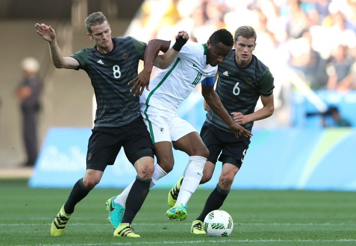 Mikel Obi being tackled by German defence