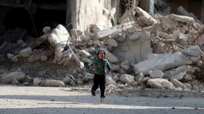 A boy runs in front of damaged buildings in the Douma neighborhood of Damascus, Syria November 26, 2015. REUTERS/Bassam Khabieh   - RTX1VYV5